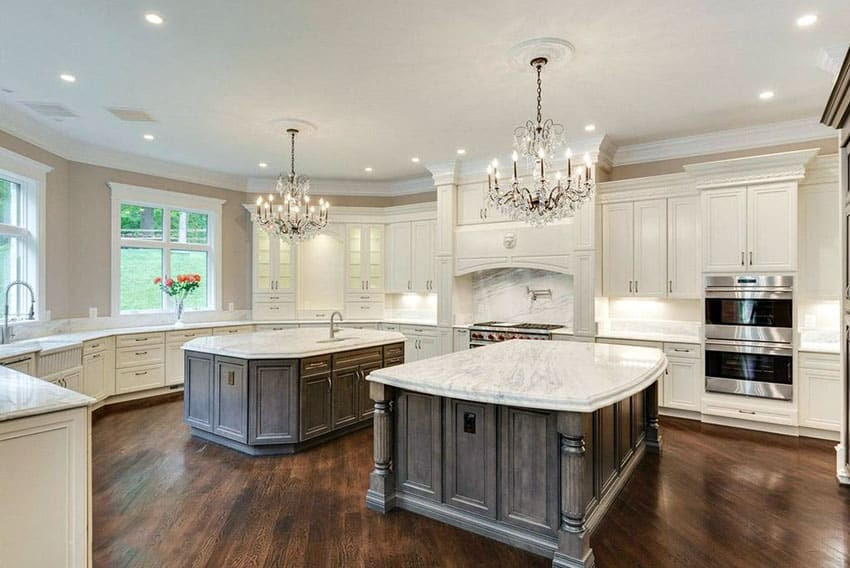 luxury kitchen with two islands chandeliers and bianco carrara marble countertops