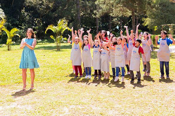 A apresentadora Carol Fiorentino sorri juntamente com as crianças participantes, que pulam de alegria