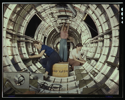 """Women workers install fixtures and assemblies to a tail fuselage section of a B-17 bomber at the Douglas Aircraft Company plant, Long Beach, Calif. Better known as the """"Flying Fortress,"""" the B-17F is a later model of the B-17, which distinguished itself i"""