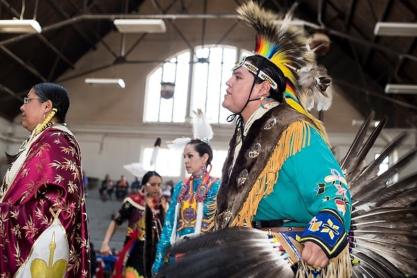 Members of Native American tribes participate in a grand entry drumming and dance ceremony  during a Spring Powwow at the UW-Madison Stock Pavillion.  Image Courtesy of Jeff Miller and the University of Wisconsin-Madison.