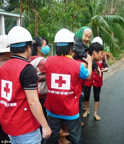 Assistance: An elderly woman is evacuated from her home by Red Cross staff in Vietnam