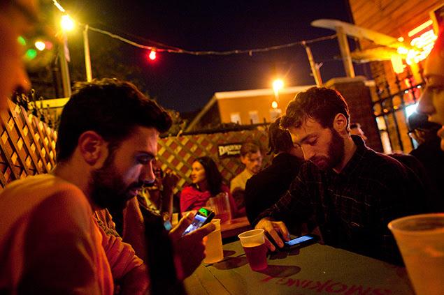 """Grupo de amigos comemora um aniversário em um bar de Nova York; para alguns, smartphones podem ter """"ido longe demais"""""""