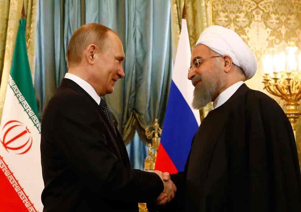 O presidente russo Vladimir Putin (esq.) aperta a mão do presidente iraniano Hassan Rohani durante encontro no Kremlin (Foto: Sergei Karpukhin/pool/AFP)