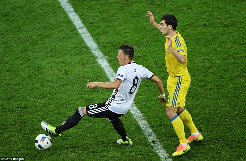 Arsenal playmaker Ozil (left) turns away from danger as he is marked byShakhtar Donetsk defensive midfielder Taras Stepanenko