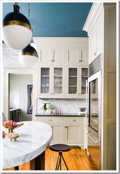 The Bronze/Hand-Rubbed Bronze finish combination on these Hicks Pendants really pops against the peacock blue ceiling in this stunning kitchen.