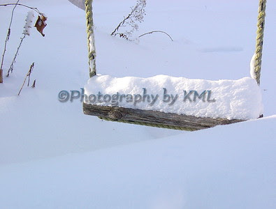 a wood swing covered in winter snow