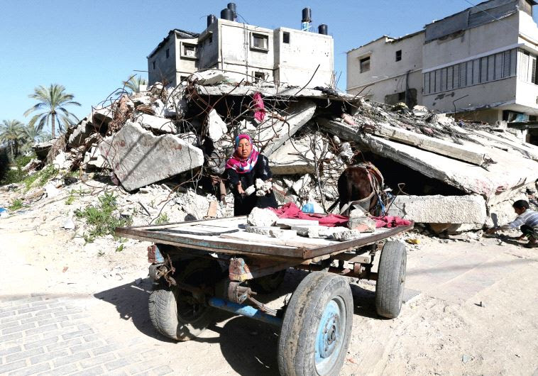 A Palestinian woman collects bricks from a house destroyed during the 2014 Gaza war (photo credit: REUTERS)