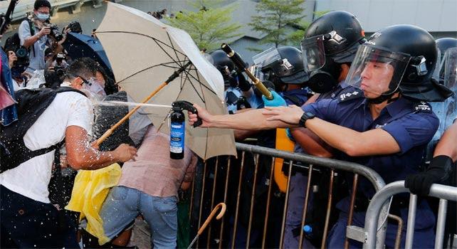 Un agente antidisturbios rocía a un manifestante con un espay de pimienta.