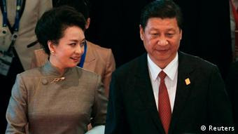 China's President Xi Jinping (C) and his wife Peng Liyuan (L) attend the Asia-Pacific Economic Cooperation (APEC) Summit in Nusa Dua on the Indonesian resort island of Bali October 7, 2013. REUTERS/Beawiharta (INDONESIA - Tags: POLITICS)
