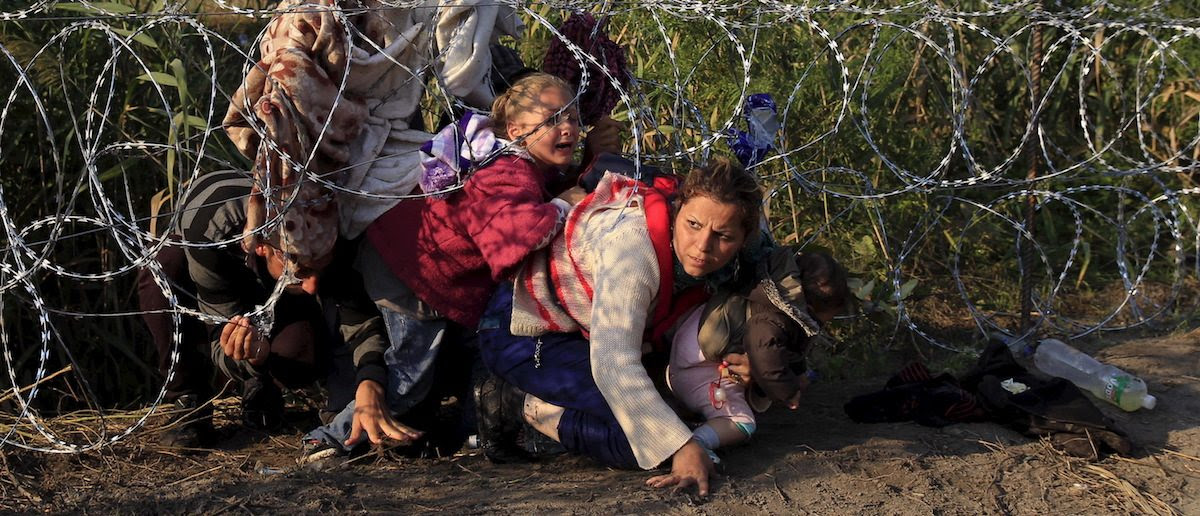 Syrian migrants cross under a fence as they enter Hungary at the border with Serbia, near Roszke, August 27, 2015. Hungary made plans on Wednesday to reinforce its southern border with helicopters, mounted police and dogs, and was also considering using the army as record numbers of migrants, many of them Syrian refugees, passed through coils of razor-wire into Europe. REUTERS/Bernadett Szabo