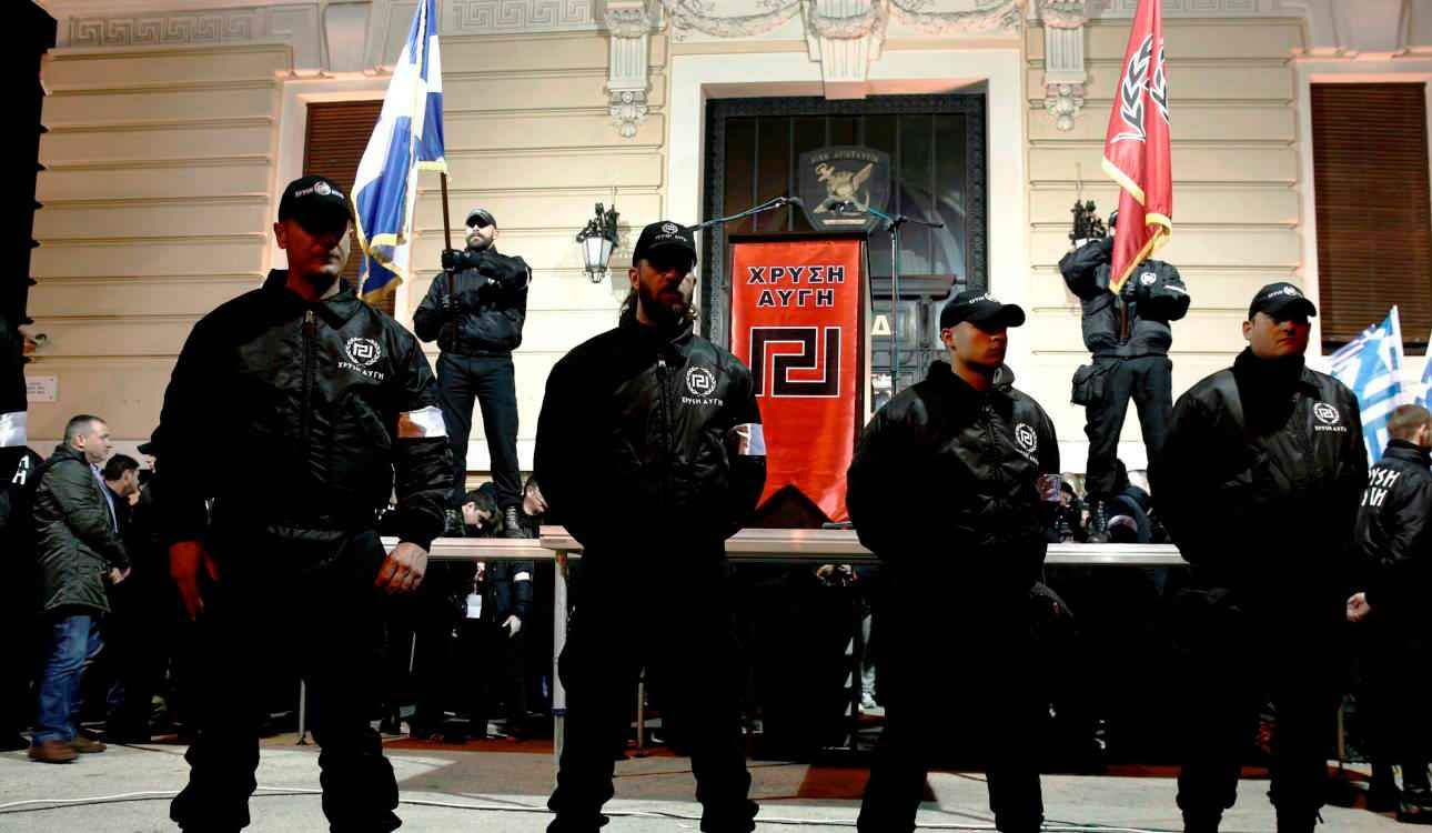 Members of the extreme-right Golden Dawn party stand around a stage during a gathering in Athens February 2, 2013. Thousands of supporters gathered to pay tribute to three Greek officers who were killed when their helicopter crashed during a crisis with Turkey over the eastern Aegean isle of Imia back in 1996. REUTERS/Yorgos Karahalis (GREECE - Tags: POLITICS CIVIL UNREST)
