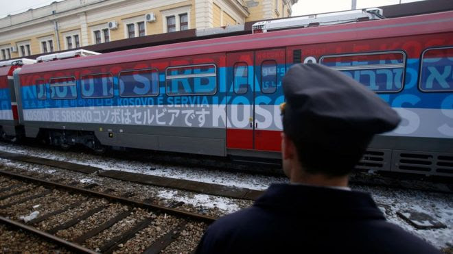 "A railroad worker stands by the first train decorated with letters that read ""Kosovo is Serbian"" written in twenty languages"