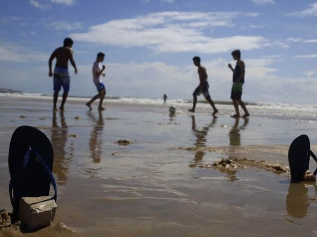Moradores e turistas jogam futebol de golzinho marcado por chinelos fincados na areia na praia de Ponta Negra, em Natal (RN) (Foto: Hassan Ammar/AP)