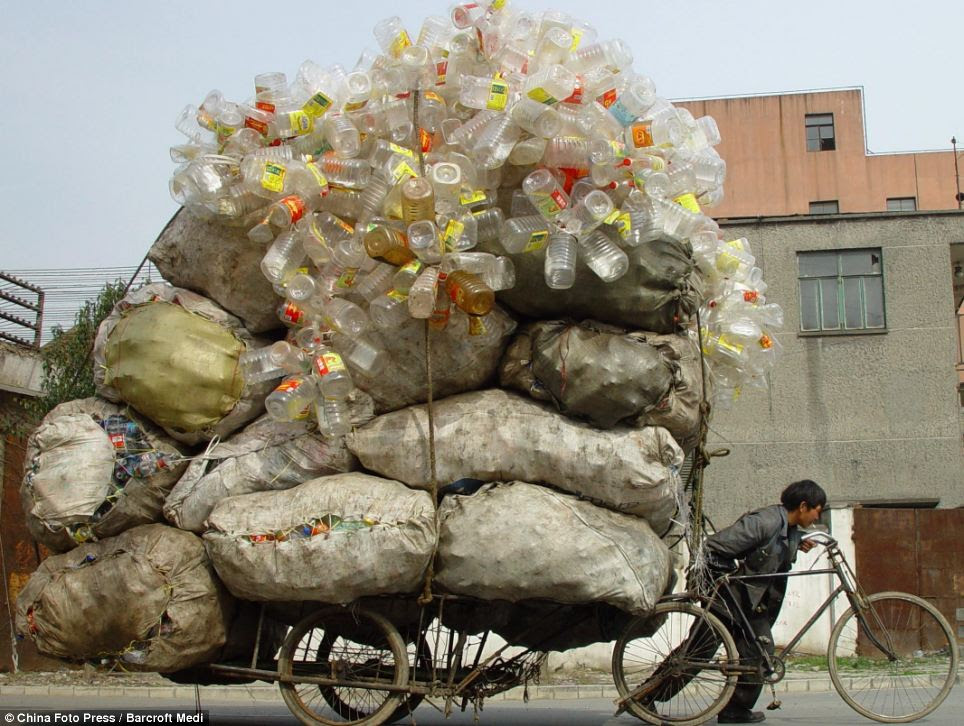 A collector of recyclable waste in pushes along his enormous plastic bottle collection in Shanghai