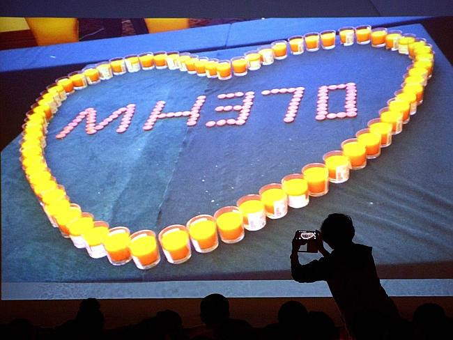Remembered...A woman takes a photo of a screen showing candles lit for relatives of passe