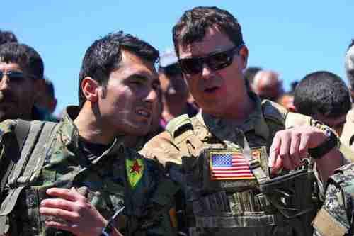 Un oficial de los Estados Unidos hablando con un luchador YPG el 25 de abril (AFP)