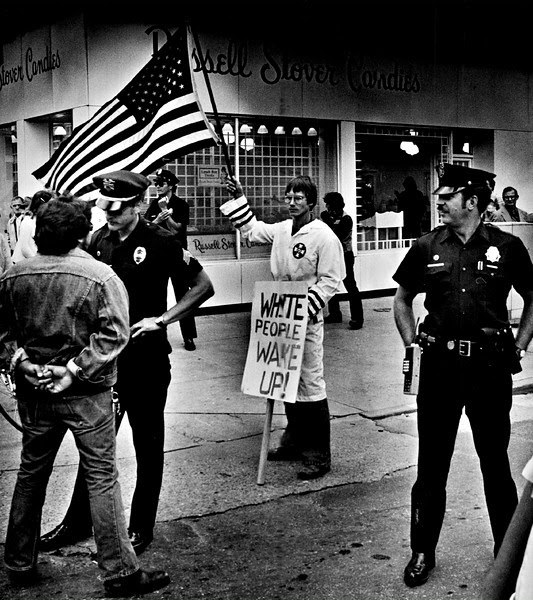 Description of  SEP 14 1979 - Denver policeman protect a flag-waving member of the Ku Klux Klan at 16th street and Court place about 11:45 a.m. Friday during a Chicano march through downtown Denver Kicking off festivities for Mexican Independence Day, celebrated Sunday. One of the marchers in confronted by a policeman, left, as he attempts to approach the Klansman. Shortly after, unidentified Klansman rolled up his sign and flag and left. (Duane Howell/The Denver Post)