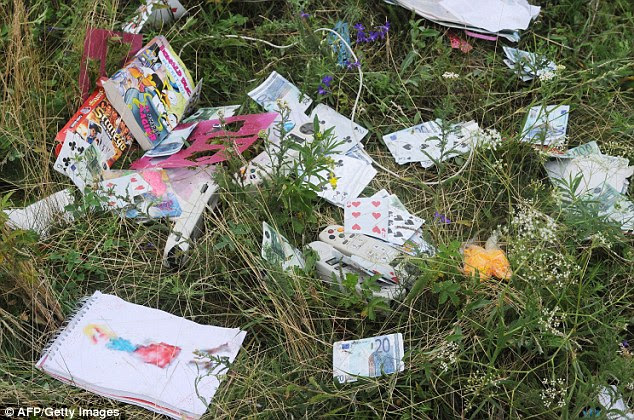 Remnants of the MH17 plane crash: cards, money and remote controls from passengers' seats lay strewn on at the scene