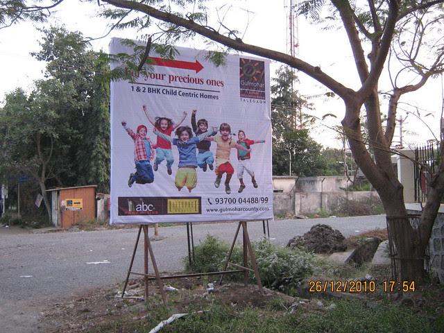 Gulmohar County, 1 BHK & 2 BHK Flats, behind Talegaon Telephone Exchange, Talegaon Dabhade, Pune 410 506  - Hoarding near Talegaon Telephone Exchange