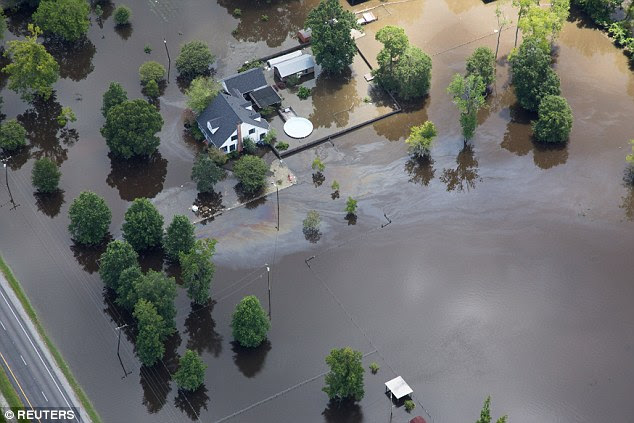 Contaminated floodwaters impact an area in Ascension Parish where some 40,000 homes have been impacted by the recent flooding, as seen in an aerial view on Wednesday