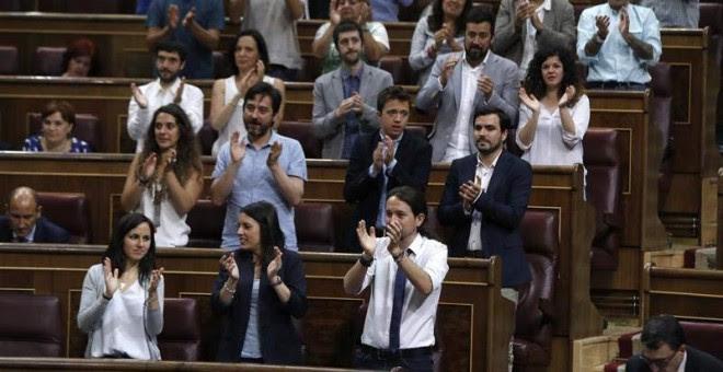 Los diputados de Podemos aplauden a uno de los suyos.   EFE
