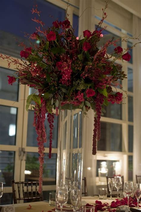 A tall centerpiece featuring red mokara orchids, burgundy