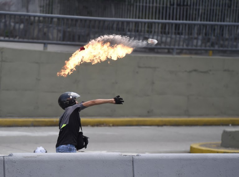 "A demonstrator against Nicolas Maduro's government throws a Molotov cocktail during clashes with riot police at eastern Caracas on April 8, 2017.  The opposition is accusing pro-Maduro Supreme Court judges of attempting an internal ""coup d'etat"" for attempting to take over the opposition-majority legislature's powers last week. The socialist president's supporters held counter-demonstrations on Thursday, condemning Maduro's opponents as ""imperialists"" plotting with the United States to oust him.  / AFP PHOTO / JUAN BARRETO"