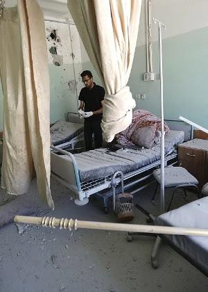 Funcionário palestino inspeciona os danos no hospital Al-Aqsa na faixa de Gaza; ataque israelense matou ao menos 4