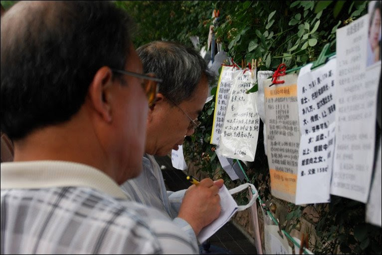 People writing down details from notices in People's Park, Shanghai