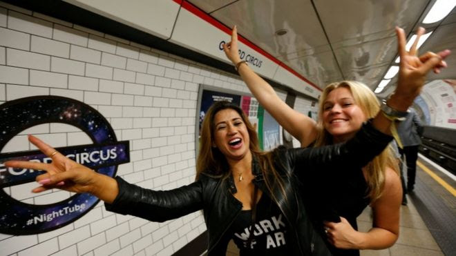 Passengers pose for a photograph as they wait for the Night Tube