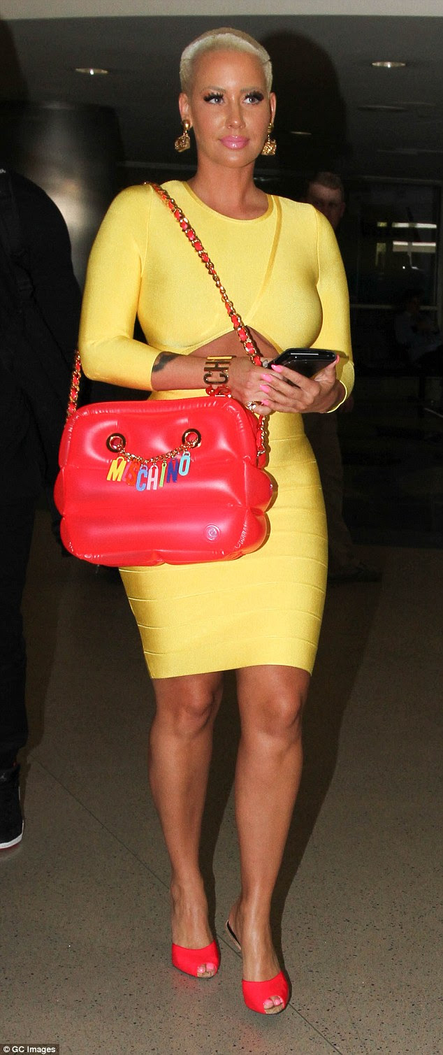 Arm candy: Amber showed off her inflatable designer bag as she strutted through the airport following her flight from Vegas