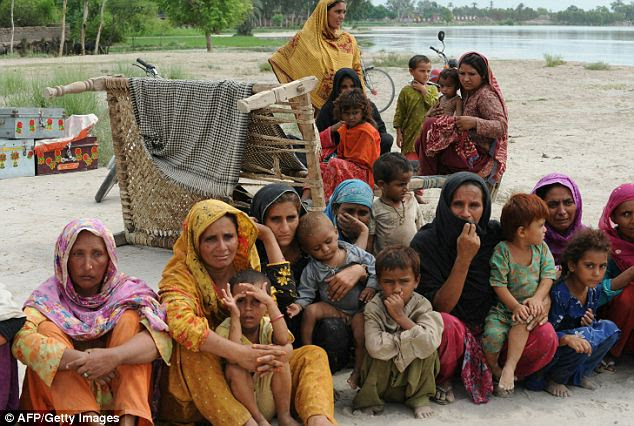 Survivors sit on a high ground at the flooded area in Pathan Wala