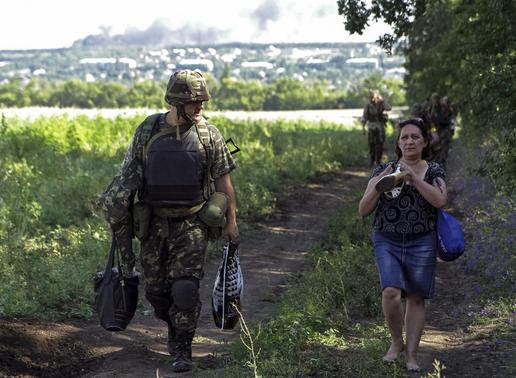 Ukrainian army soldier from battalion 'Aydar' helps a local resident as she leaves the village of Metalist near the eastern Ukrainian city of Luhansk July 11, 2014. UREUTERS-Viktor Gurniak
