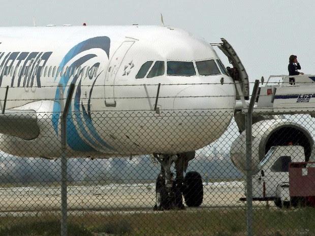 Uma pessoa ao telefone na escada de acesso a avião sequestrado (Foto: Yiannis Kourtoglou / Reuters)