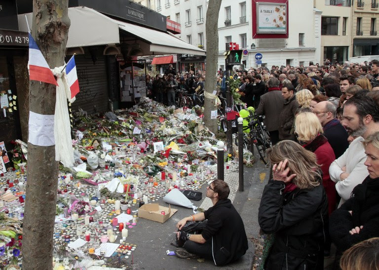 People observe a minute of silence on November 16, 2015 outside the La Belle Equipe on Rue de Charonne in the XI arrondissements in Paris, to pay tribute to victims of the attacks claimed by Islamic State which killed at least 129 people and left more than 350 injured on November 13. (AFP PHOTO/JACQUES DEMARTHON)