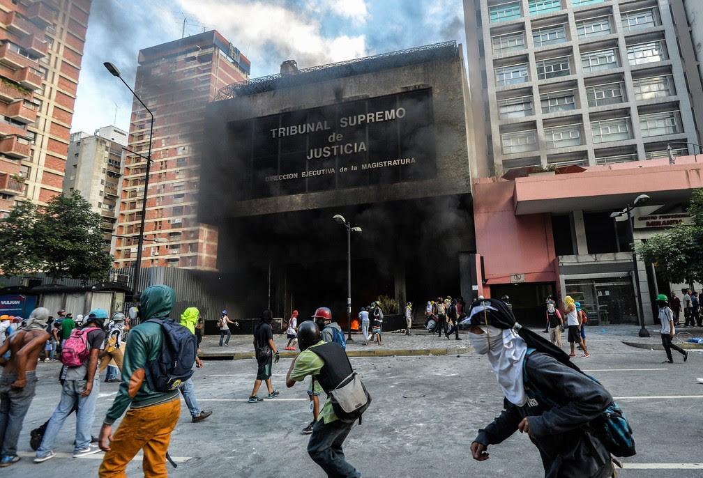 Manifestantes opositores atacam prédio administrativo do Tribunal Superior de Justiça da Venezuela nesta segunda-feira (12) em Caracas (Foto: LUIS ROBAYO / AFP )