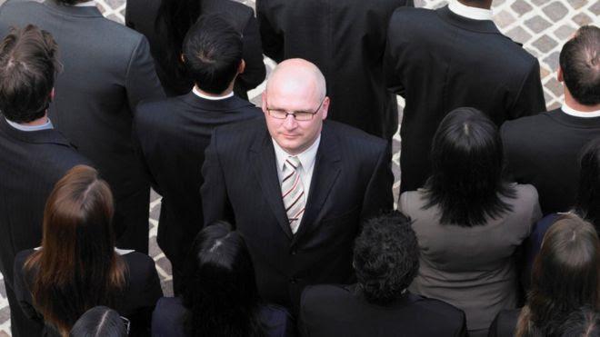 Hombre calvo en medio de un grupo de personas con cabello