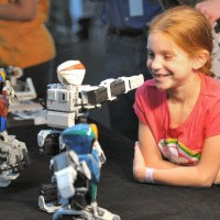 An audience member at RoboGames is entranced by robot dance moves. Photo: Dave Schumaker