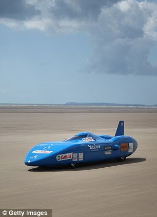 Building up speed: Joe steers the car along the flat Pendine Sands before the wheel sheered off