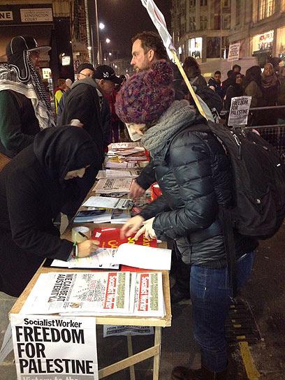 מחתימים אנשים לפעילות בהפגנה בלונדון (צילום: רונה זינמן)