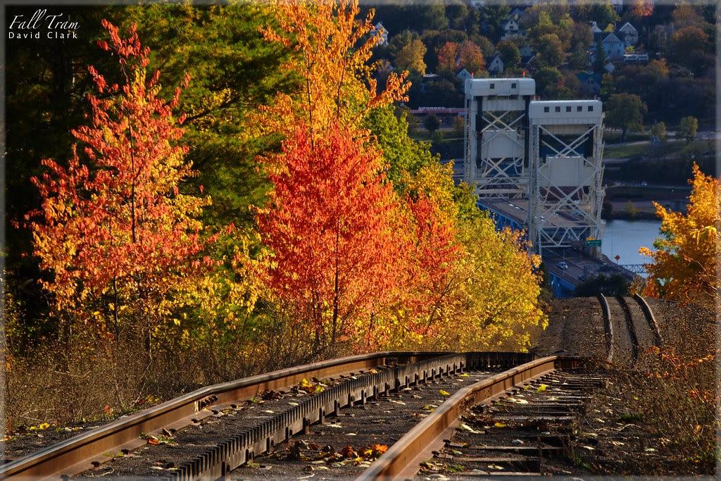 A bright fall color scene with a rail line leading down a hillside, towards the Portage Lake Lift Bridge.