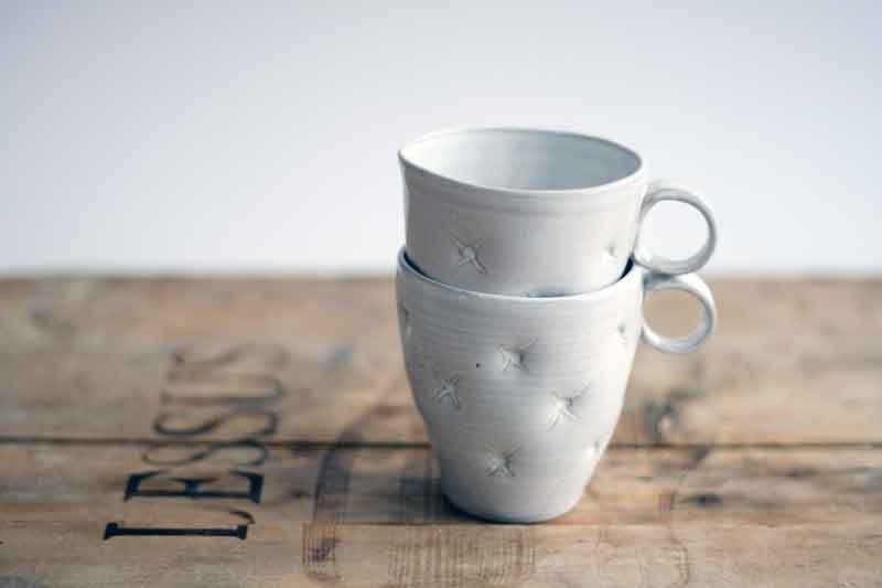 Cute white ceramic cup, handmade and decorated with pillow effect