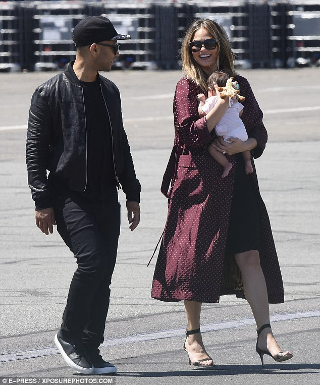 The smiles say it all! Chrissy Teigen and John legend shared a joy-filled glance as they arrived in Paris with baby daughter Luna on Saturday for their first vacation as a family of three