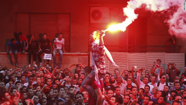 People shout slogans and light flares in front of the U.S. Embassy in Cairo.