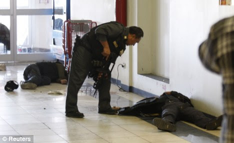 Bloody warfare: In one of the latest Mexico shootings a police officer investigates the aftermath of an incident at a shopping centre in Ciudad Juarez