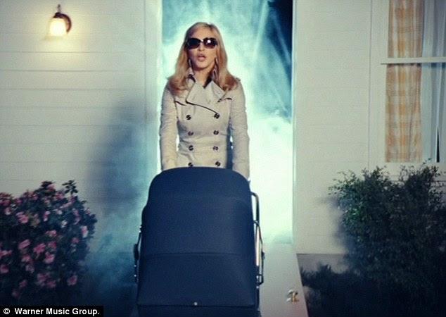 Aqui é Madonna!  A megastar é visto pela primeira vez empurrando um carrinho de bebê de uma casa surburban sobrenatural procura, neste momento ela está estranhamente embrulhado