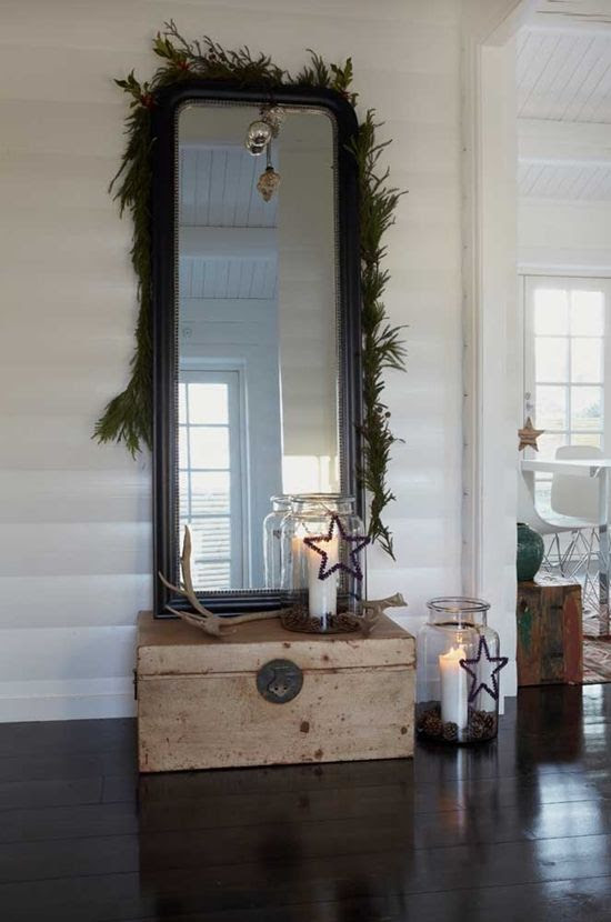 Impromptu Holiday arrangement: green garland, stars, mirror, chest, candles, driftwood. in a small corner:  reflects windows, adds space, texture and calm to room.