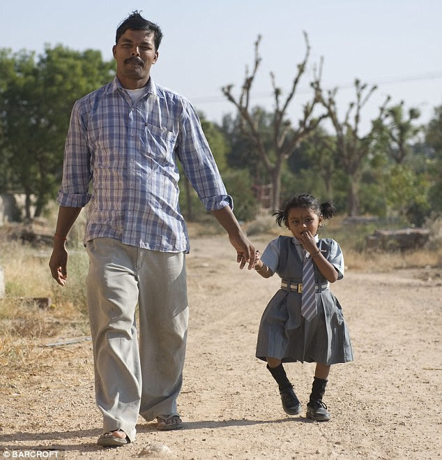 Daddy's girl: Lakshmi and her dad Shambu at their home this month. Lakshmi's parents are still fearful for her future, despite the success of the operation