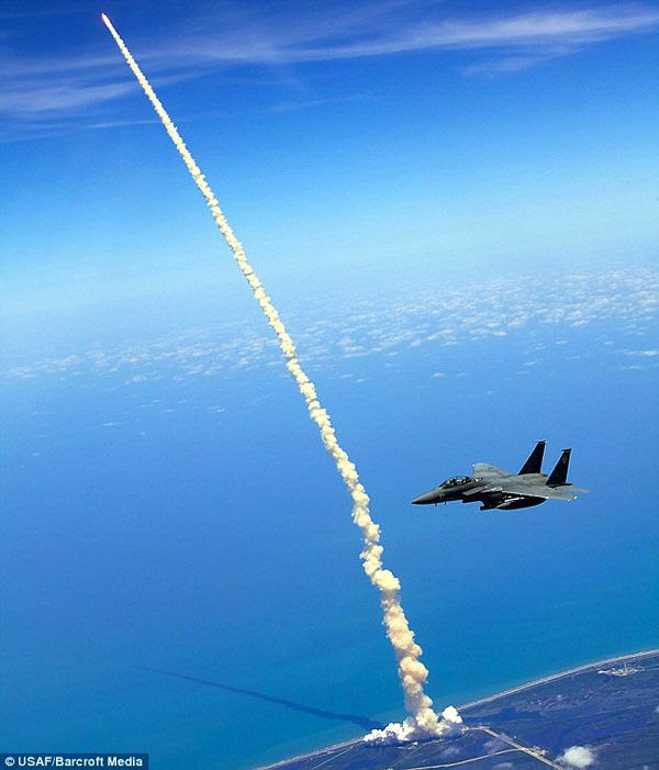 An F-15E Strike Eagle patrols the skies above Kennedy Space Center...as space shuttle Atlantis launches on flight STS-132 on May 14, 2010.