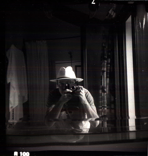 reflected self-portrait with Brownie Starmatic camera and borrowed hat by pho-Tony